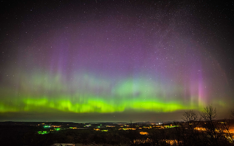northern lights of purples, blues and greens, out over the water