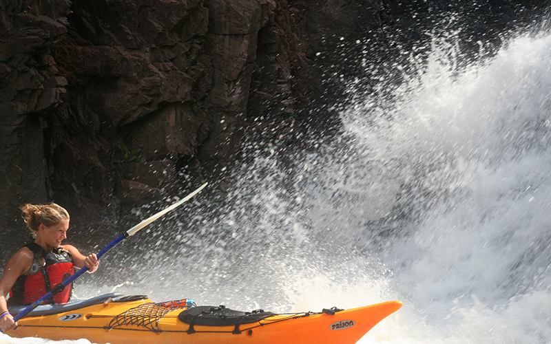 girl in a yellow kayak paddling the rapids