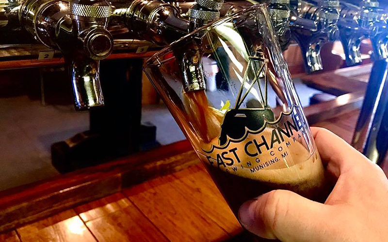 a glass of very dark craft beer being poured from the tap, logo on the glass
