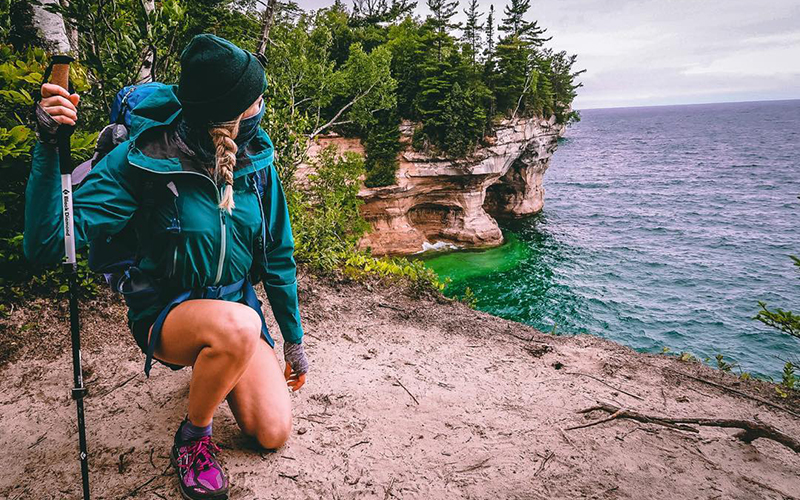 person hiking the lake superior shoreline water is aqua blue