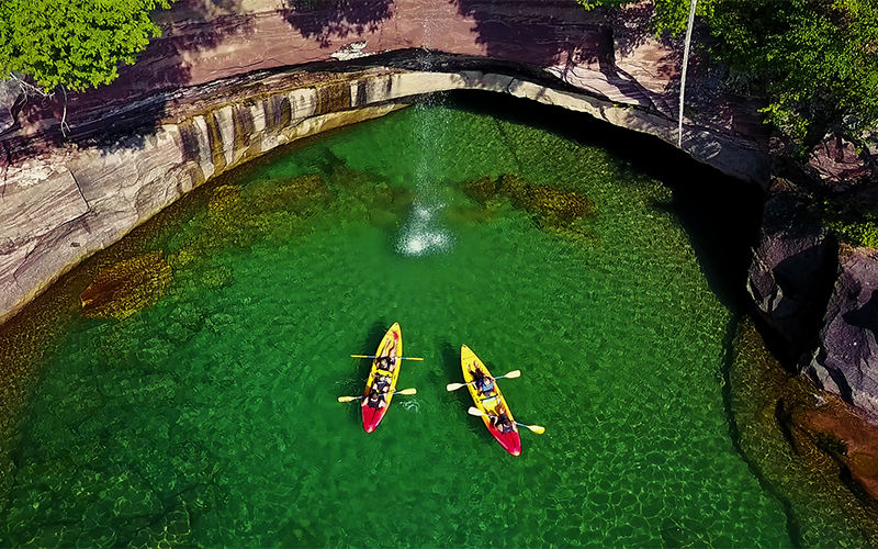 aerial view looking down on kayakers by the cliffs - water is gree