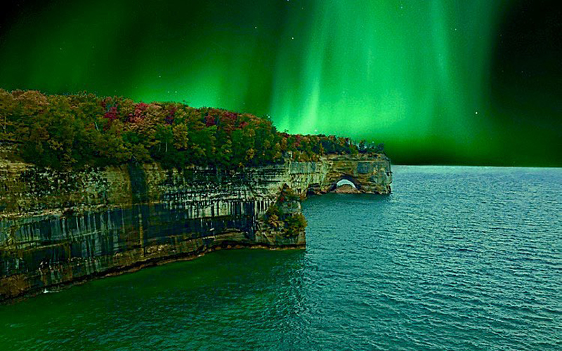 beautiful northern lights of green over pictured rocks and water is greenish blue