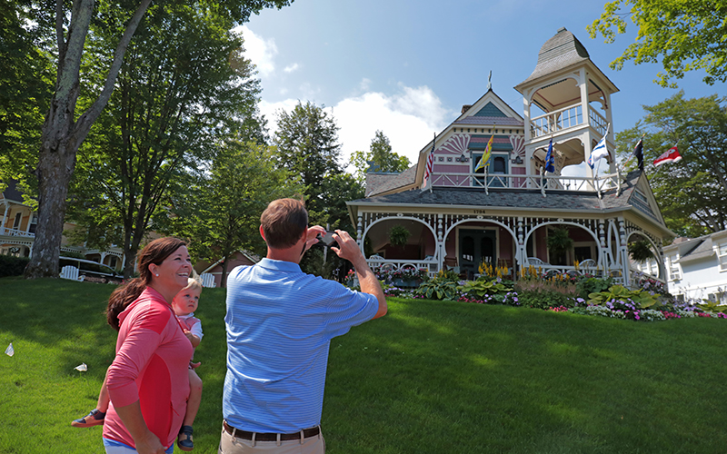 guy taking photo of historical home, wife and daughter looking on