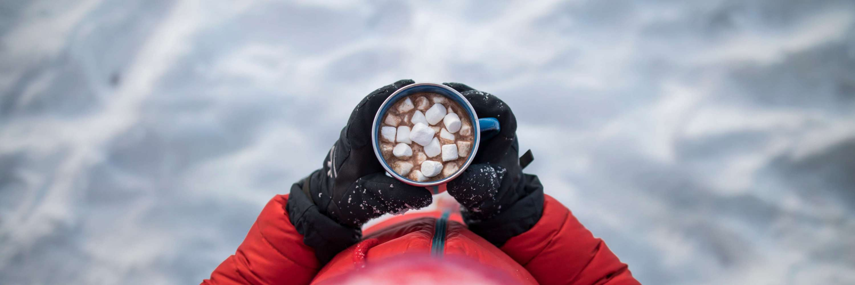 Child holding hot chocolate outside in the snow