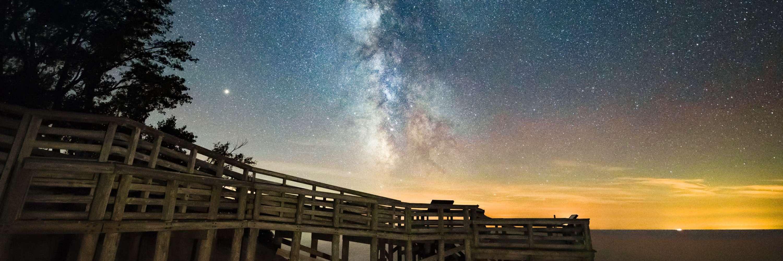 Scenic overlook on Lake Michigan under Milky Way dark sky.