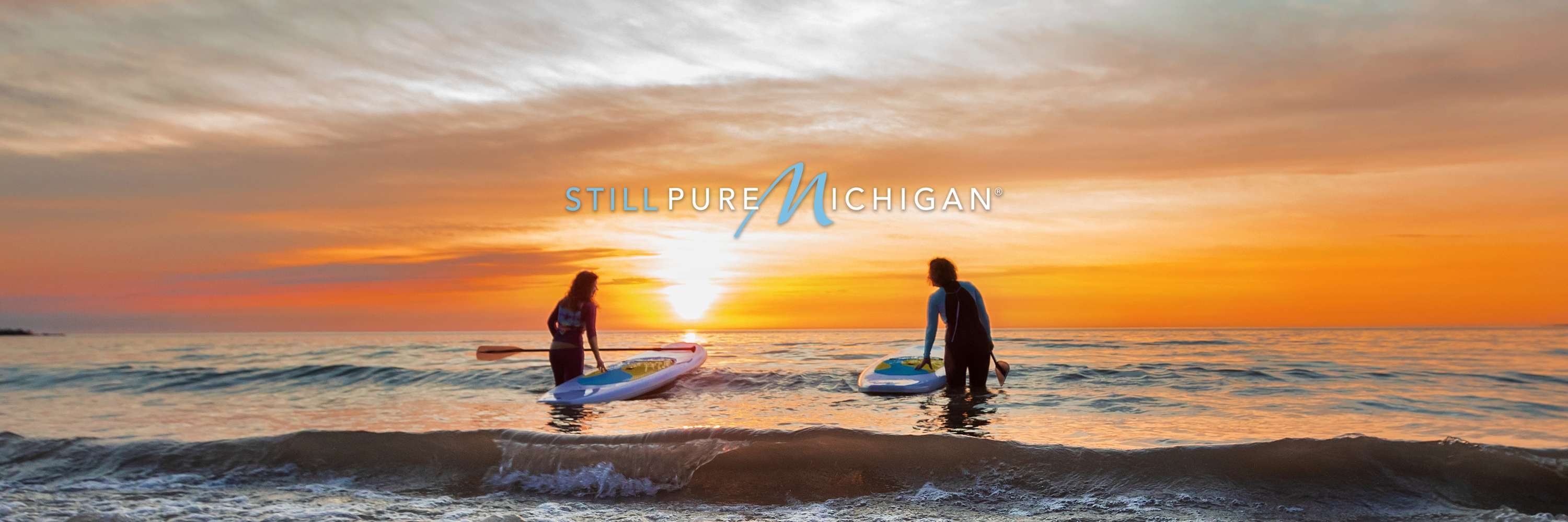 "Paddle boarders walking through Great Lakes waves with logo that reads ""Still Pure Michigan."""