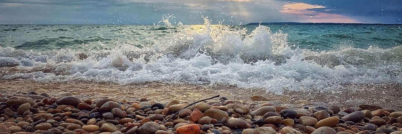 waves crashing to shore on beautiful colored rocks