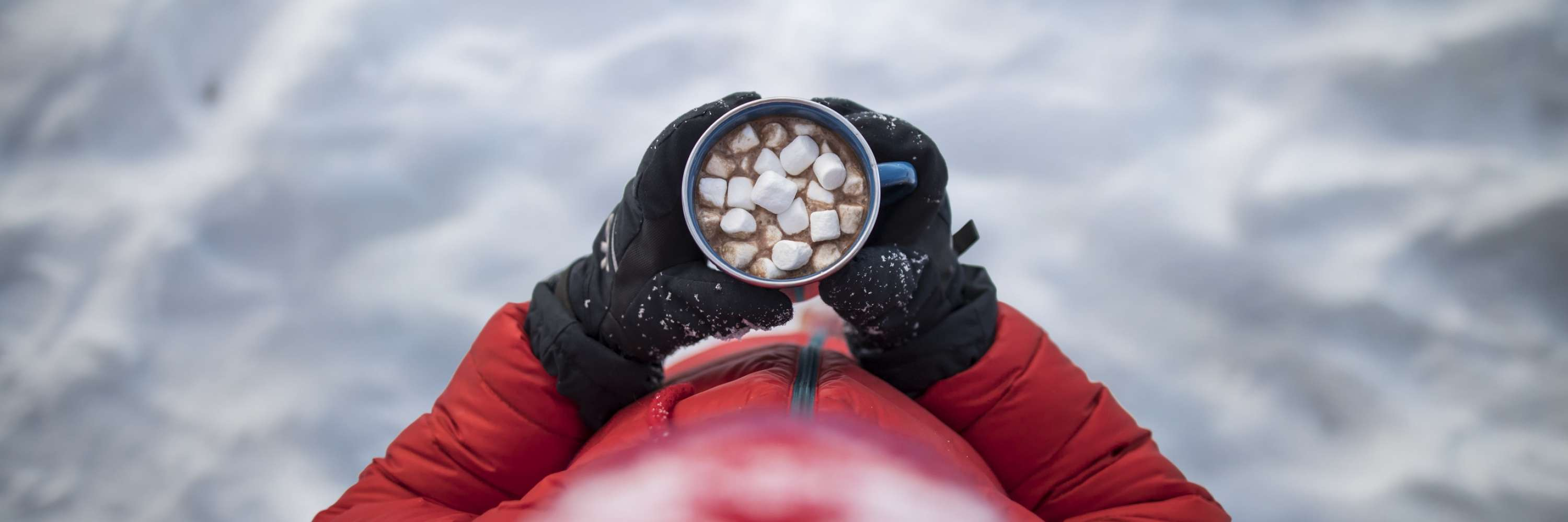 child dressed in red holding hot cooking, view looking down, snow on the ground, marshmallows in hot coco