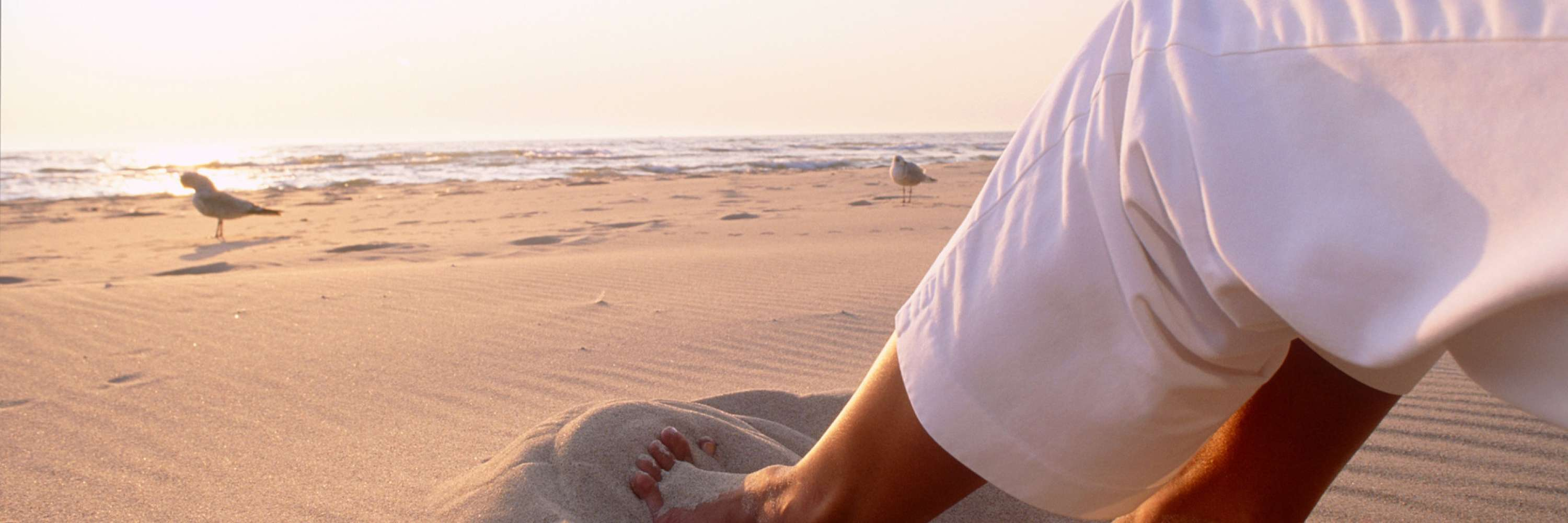 person wearing white pants with feet in the sand