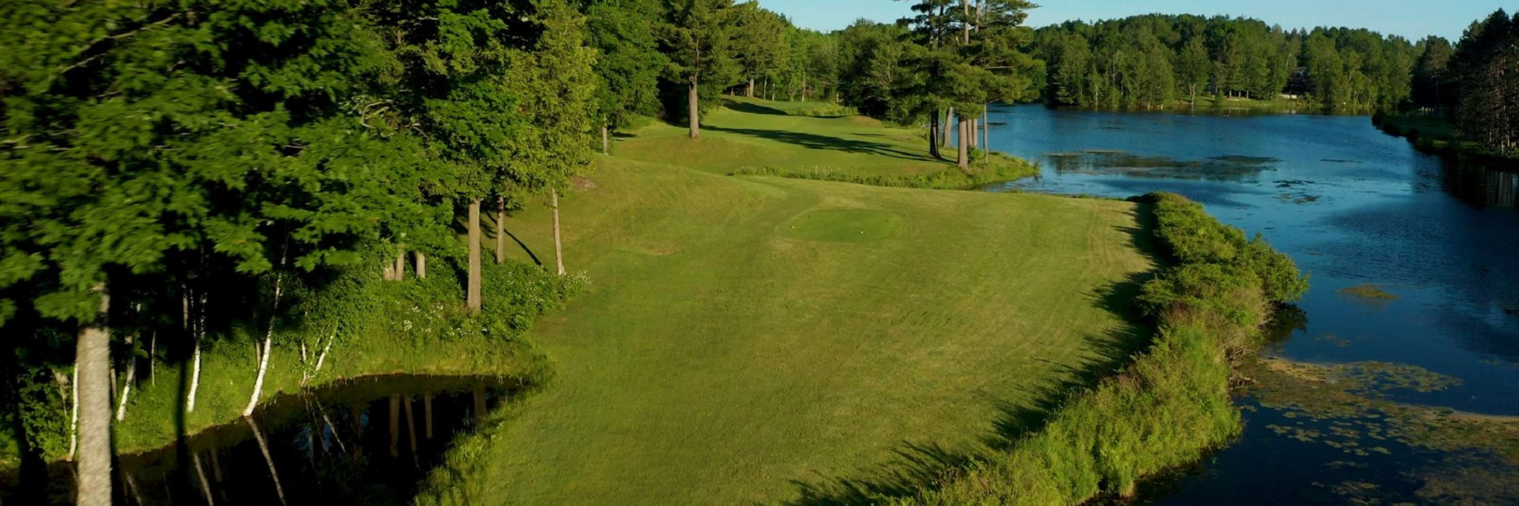 aerial view of gold course sunny day pond behind the course
