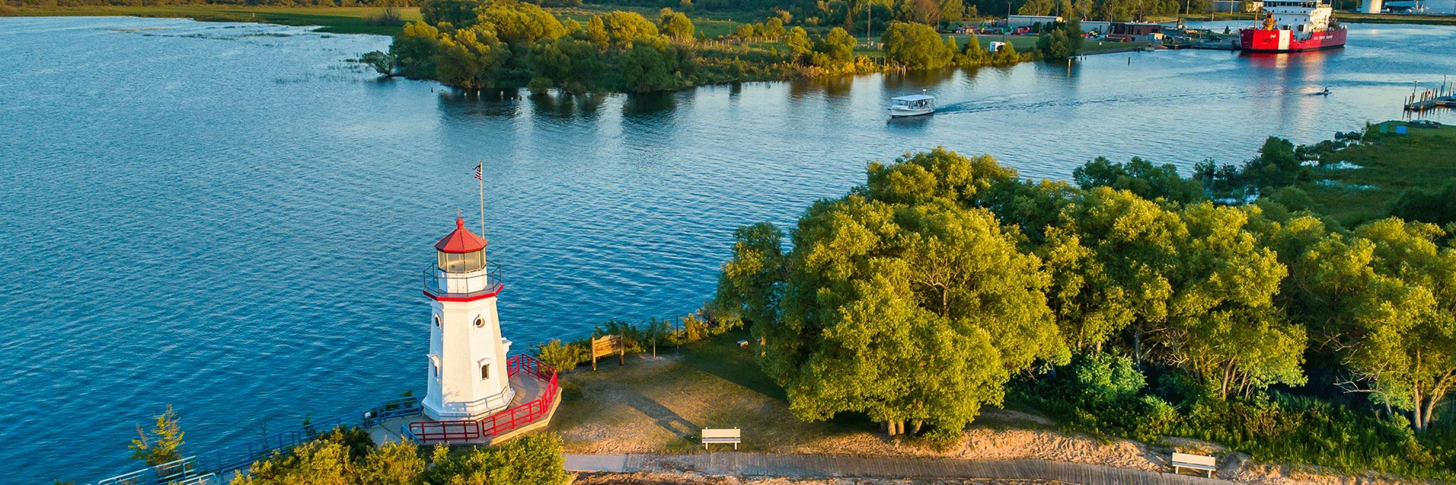 aerial view of lake with lighthouse on the corner of the waterway