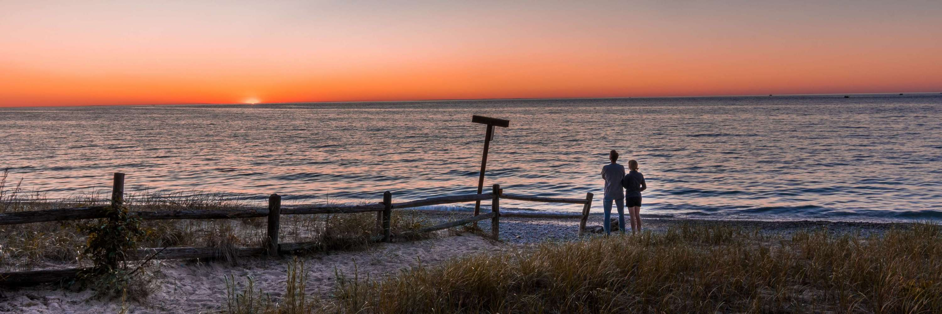 Couple watching the sunset over a Great Lake in Michigan