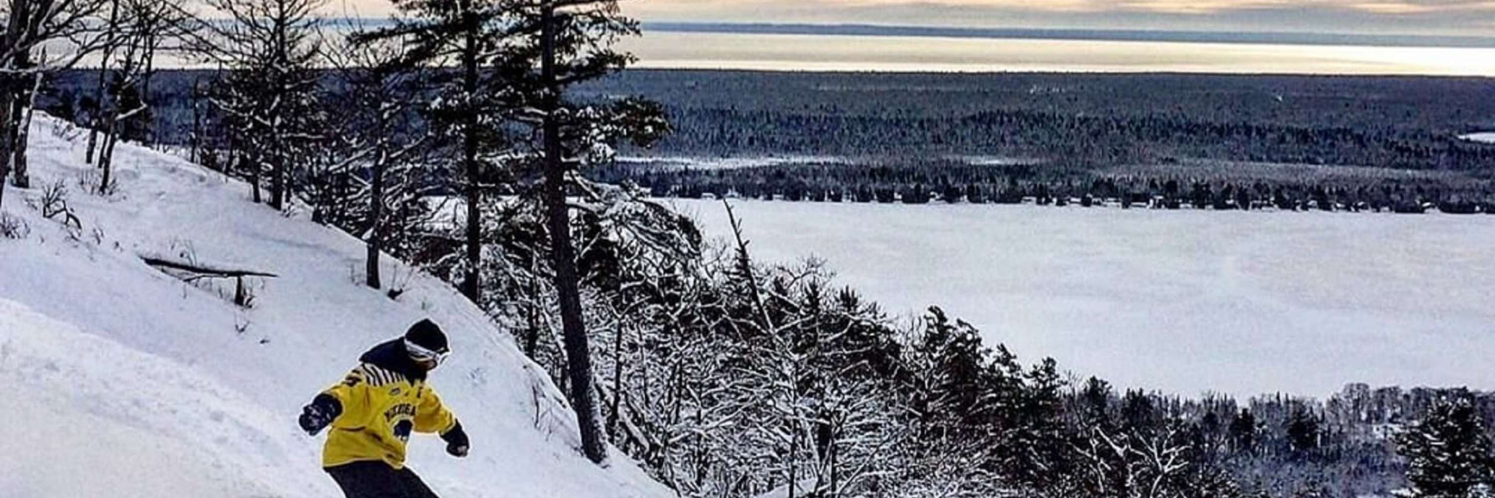 skier down the mountain with the lake in the distance, snow covered pines