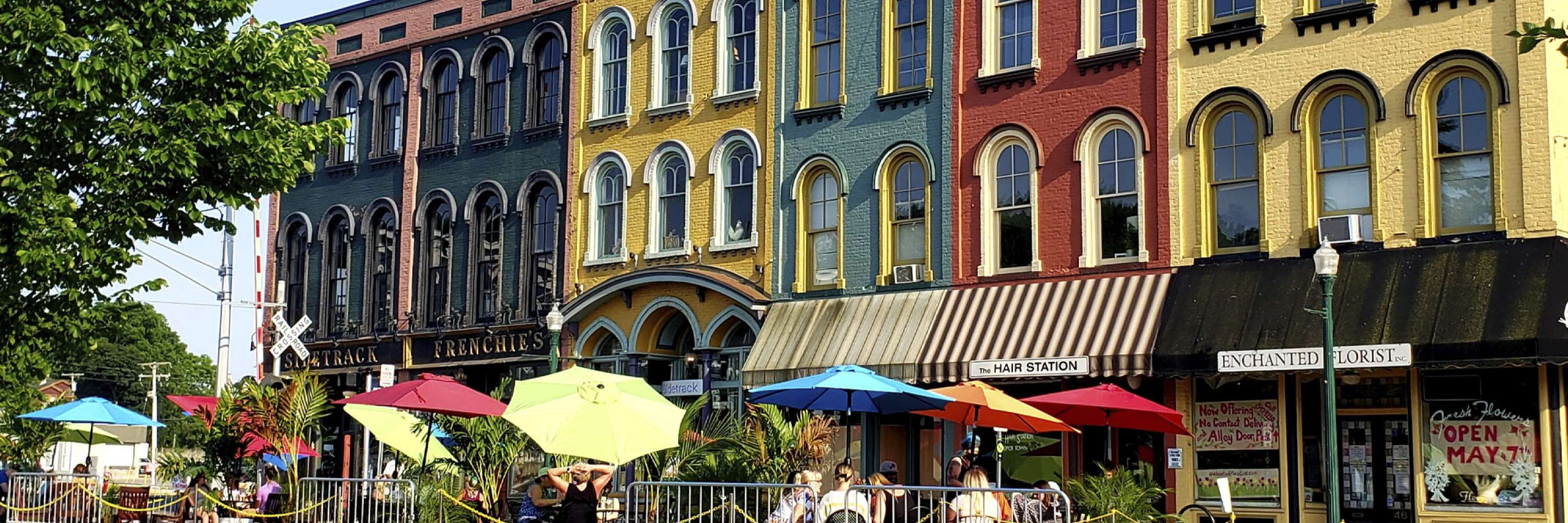 colored buildings in depot town with colored umbrellas on tables outside
