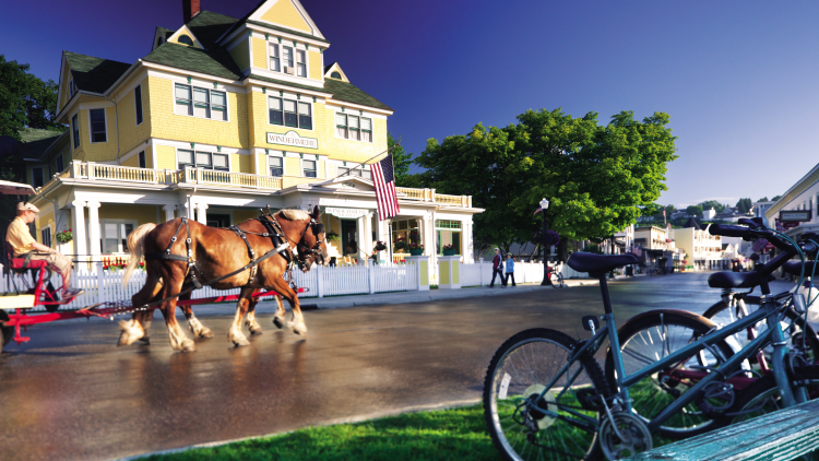 Horse drawn carriage passing front of a Victorian hotel on Mackinac Island