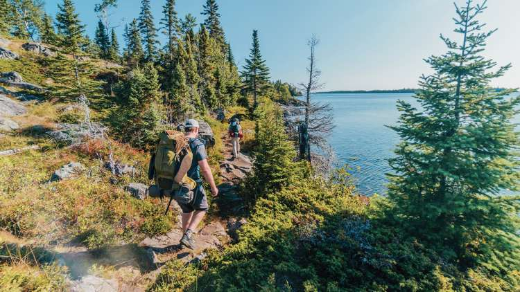Hiker walking along path overlooking a lake