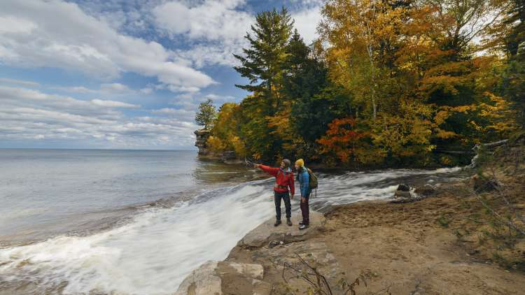 Hikers standing by waterfall on shores of Lake Superior