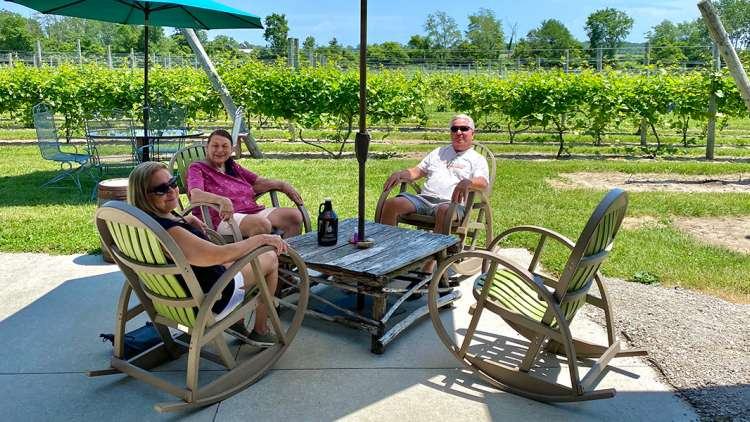 Friends sitting around an outdoor table at a vineyard.