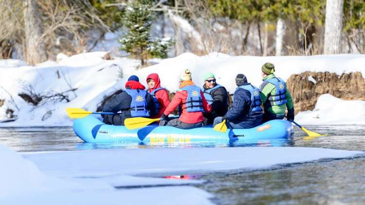 people in a floating raft on the river in the winter, snow on the sides
