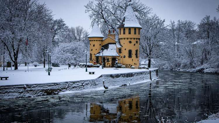 gold castle along the river covered in snow with trees all around