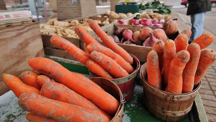 carrots, potatoes and other vegetables in pots on a table at the outdoor market
