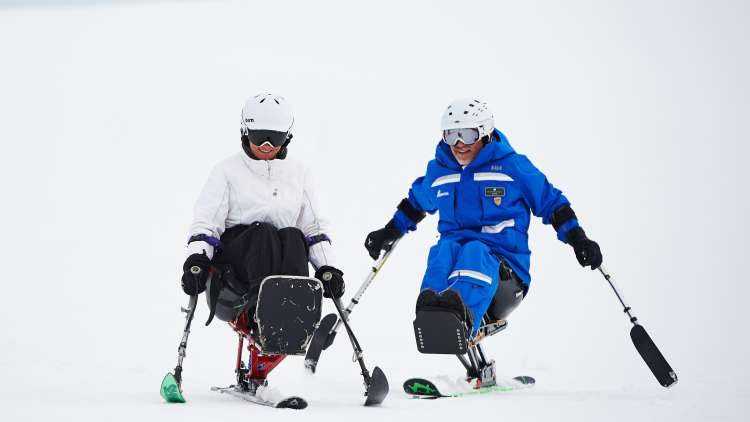 Skiers on accessible sit skis