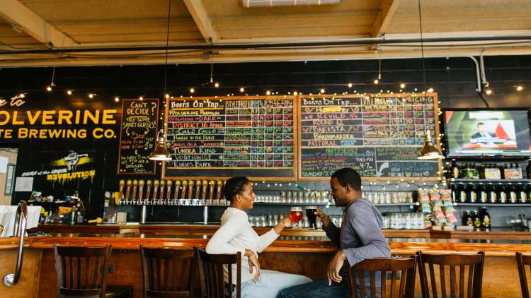 two people sitting at the bar, facing each other, drinking a craft beer, chalkboard behind the bar with all the drinks and specials listed, courtesy Destination Ann Arbor