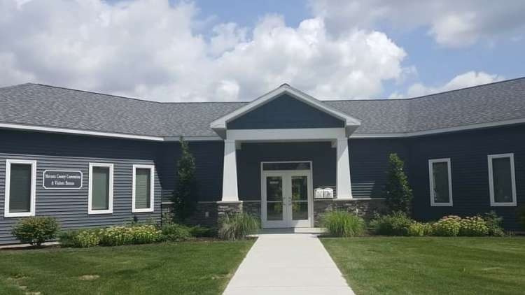 gray welcome center with green grass and sidewalk up to the center