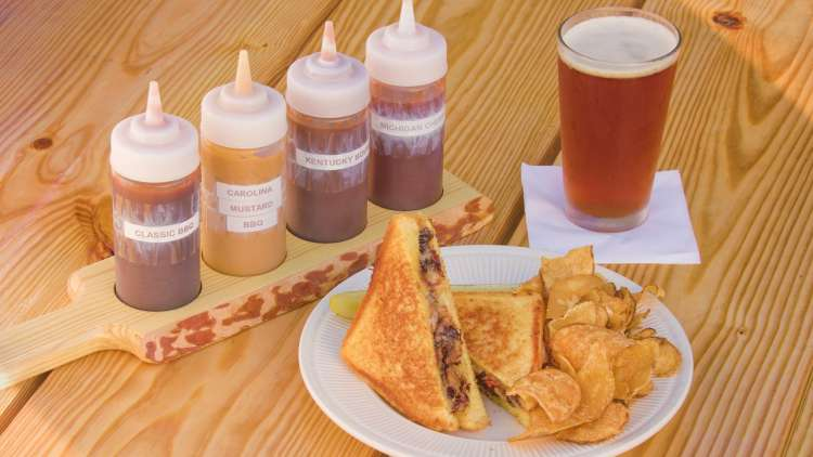 tray of 4 sauces, sandwich and chips on a plate and a glass of beer