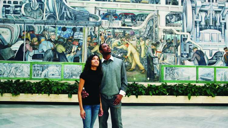 A couple viewing a mural at the Detroit Institute of Arts