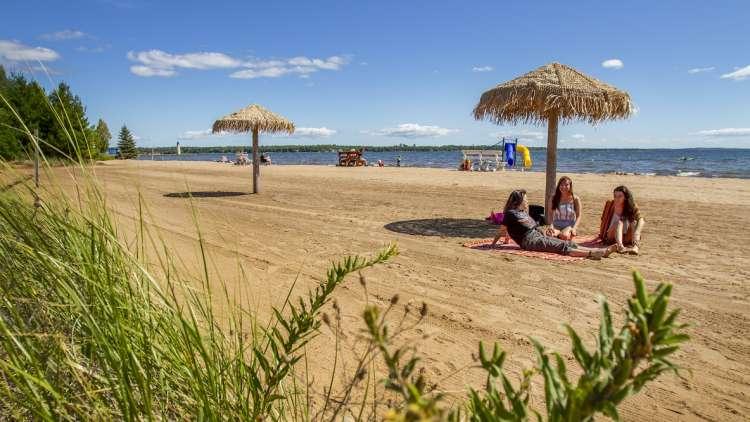 girls sitting on the beach under an umbrella