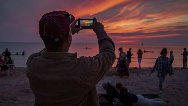 guy on the beach taking a picture at sunset