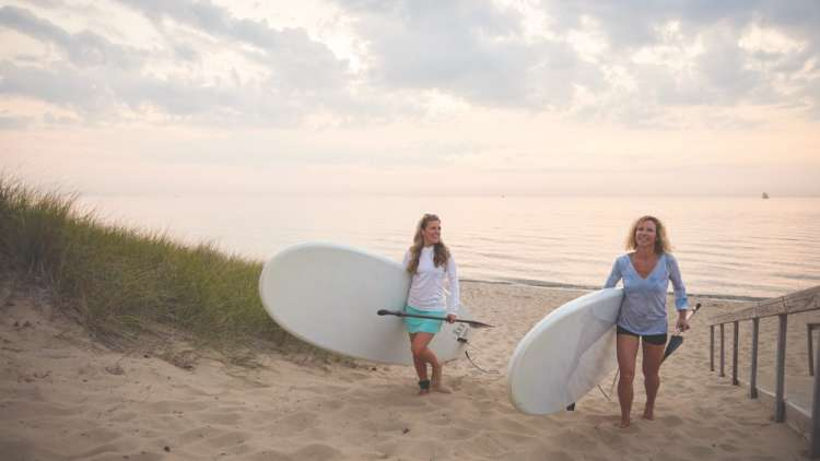 two girls with paddle boards on the beach