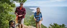 Hikers with dog on trail over Great Lakes coastline