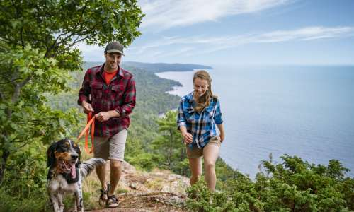 Couple and dog hiking along great lakes