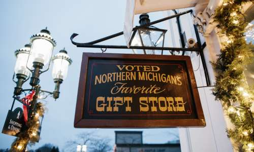 "Hanging sign outside store that reads ""Voted Northern Michigan's Favorite Gift Store."""