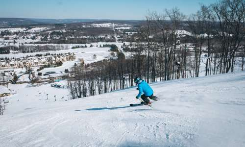 Man skiing down Boyne Mountain ski run