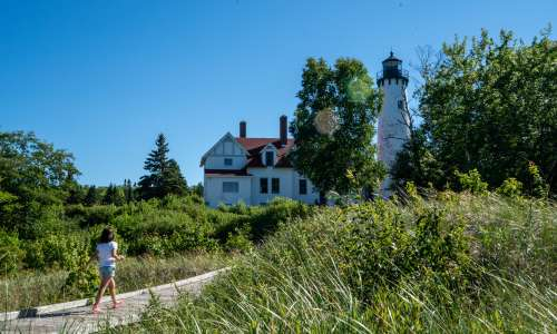 Girl walking by Point Iroquois Lighthouse