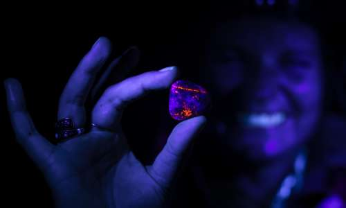 Woman holding Yooperlite rock under UV light