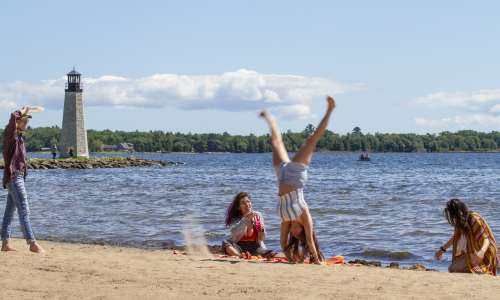 A girl doing a cartwheel on a beach in Escanaba