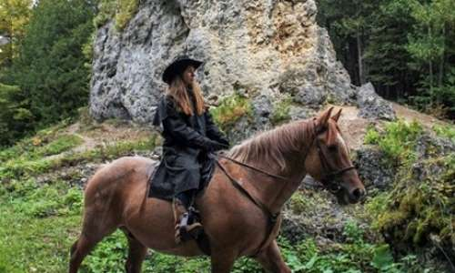 Woman riding horse on Mackinac Island trail