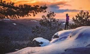 Woman snowshoeing on peak of Sugarloaf Mountain in the Upper Peninsula.