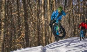 Fat tire biker doing a trick in the air.