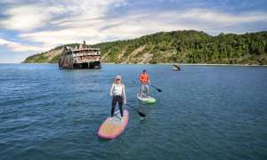 People paddle boarding on great lake next to shipwreck