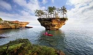 Woman kayaking by Turnip Rock