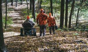 Hunter in track chair on forest path