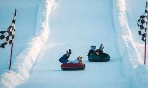 Children tubing down snowy hill