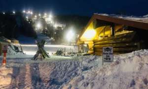 lodge lit up with lights, night skiing in the background, pack of skis standing up in the lawn