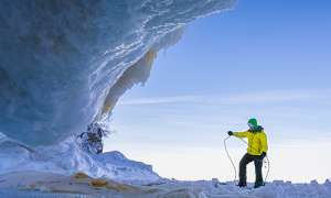 Person preparing to climb at base of ice formation