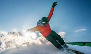 Skier kicking up snow on hill